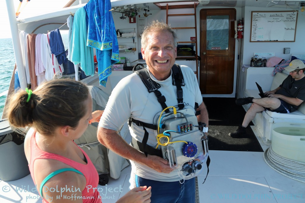 Dr. Adam Pack, an associate professor at the University of Hawaii at Hilo and long-time colleague of the Wild Dolphin Project, wears a CHAT box prior to entering the water.  Georgia Tech team members Celeste Mason and Dr. Thad Starner check the device physically, and via computer, before the system goes in the water.